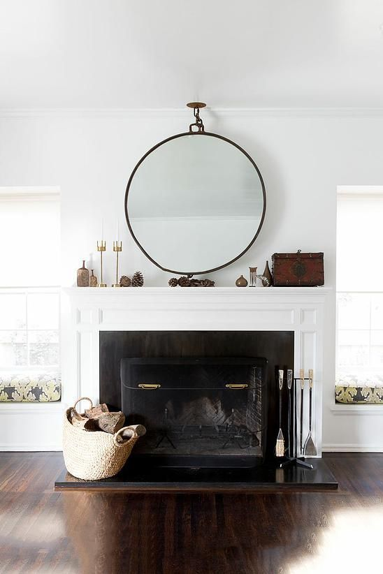 Oversized round mirror above mantel Family Living Rooms