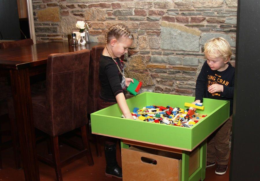 Houten Lego tafel als kinderhoekje in restaurant. Handig met opstaand randje en grote opbergbak.