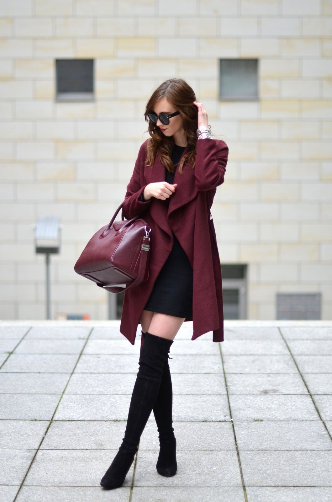 63a453b4ed94 Barbora Ondrackova shows us another way to wear thigh high boots, wearing  this pair with a little black dress and a matching burgundy coat and bag.