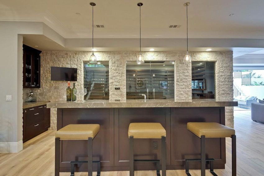 Home Bar With Light Wood Flooring, Stone Accent Wall And Wine Cellar