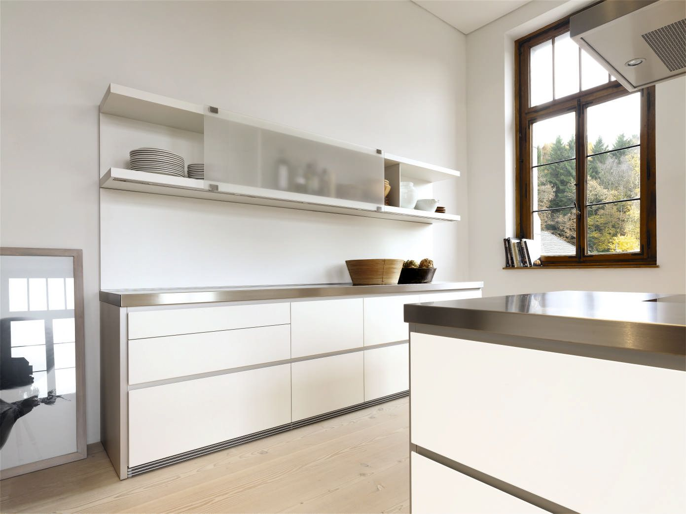 bulthaup b1 with Alpine white lacquered fronts, aluminum recess profiles, sliding glass doors on the shelving system, stainless worktops and aluminum plinths.