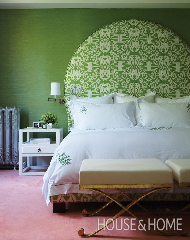 An oversized upholstered headboard against green grasscloth walls makes the beds crisp white bedding look even
