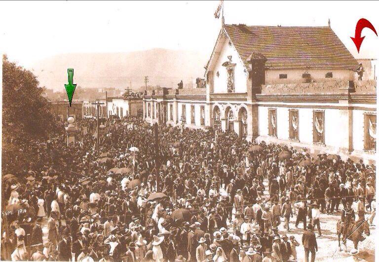 Gente frente al Colegio Civil, Septiembre de 1910, en la Celebración del Primer Centenario de la Independencia de México. indique con una flecha color verde el recién inaugurado, Monumento al Dios Bola y con una flecha color rojo a una persona que parece ser un fotógrafo en la azotea del Colegio Civil