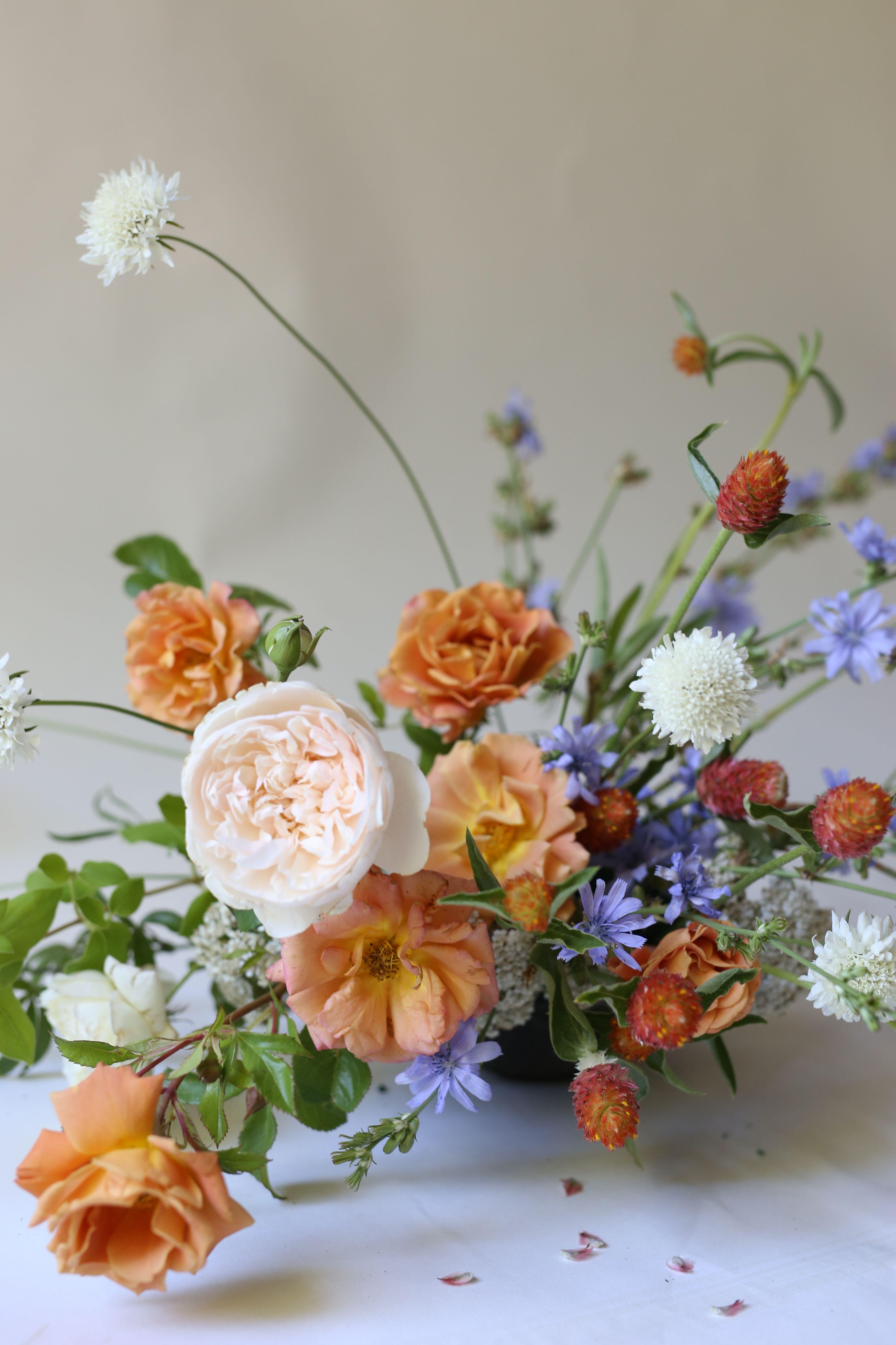 Orange, peach & lilac centerpiece Floral arrangements