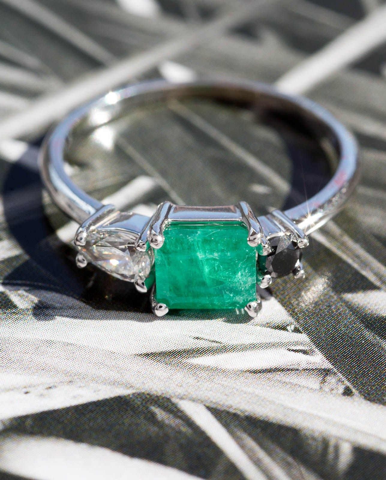 This Custom Emerald, Black and White Diamond Ring features  a crazy-unique, vintage emerald, complemented by ethical white and black diamonds, forming a design that fits the wearer's sporty yet elegant personality and style perfectly.
