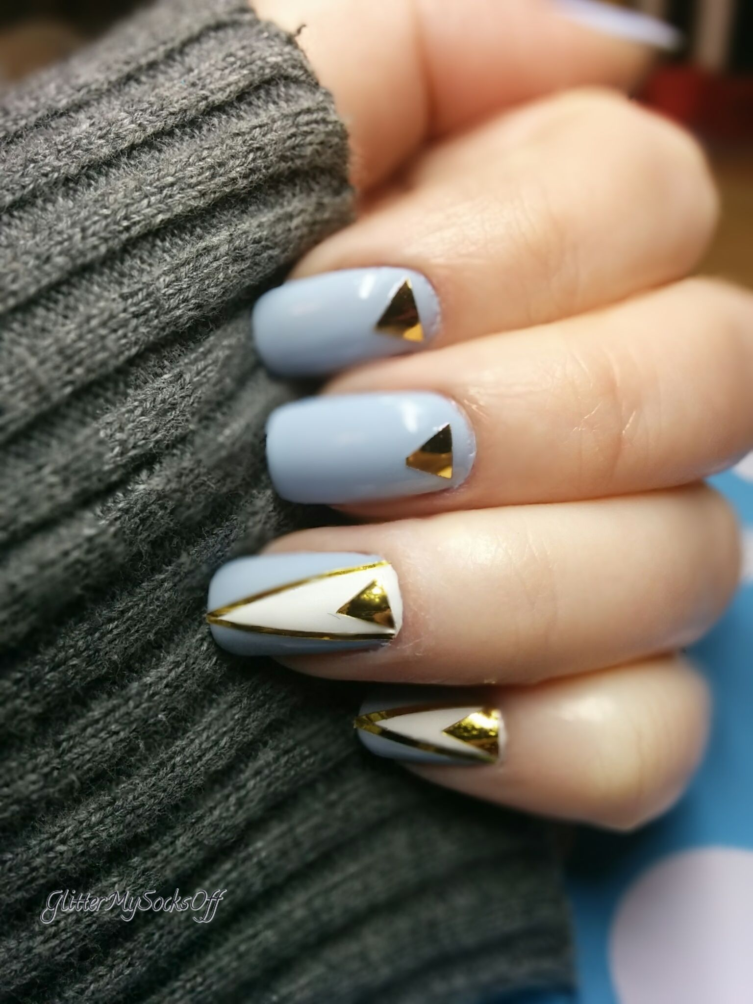 Light blue nails with triangle nail art in white and gold
