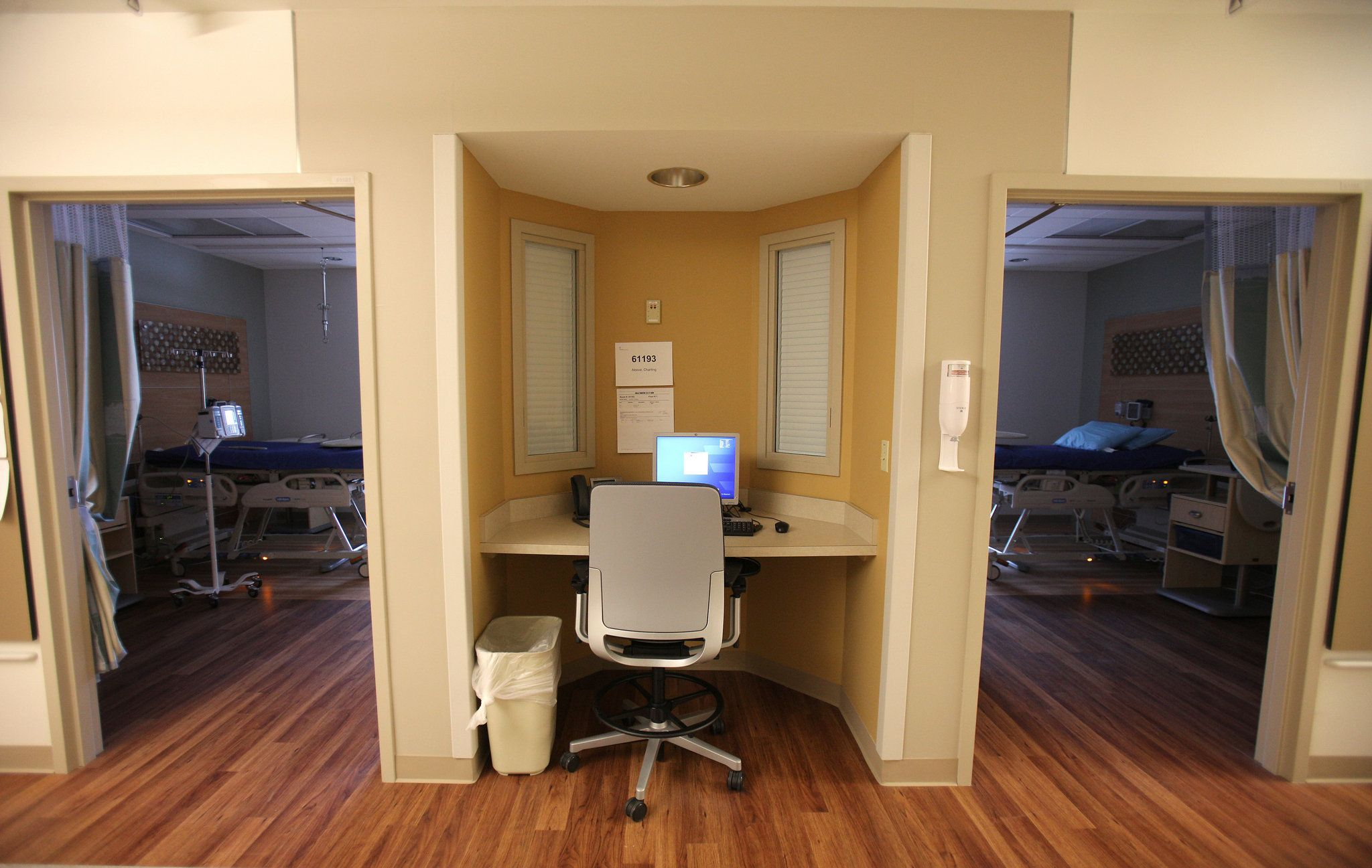 A Nurse Station Is Nestled In An Alcove Between Two Patient Rooms