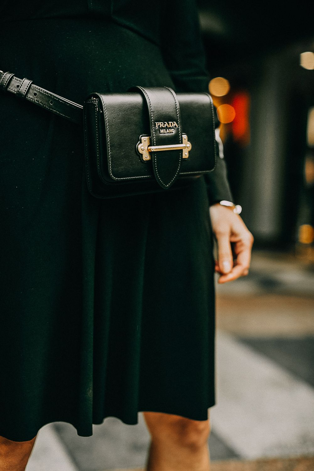 05e0c28cf326 Belt Bags, styling a Prada cahier belt bag and crossbody bag with a black  dress by Norma Kamali paired with sock booties by Stuart Weitzman on blonde  woman, ...