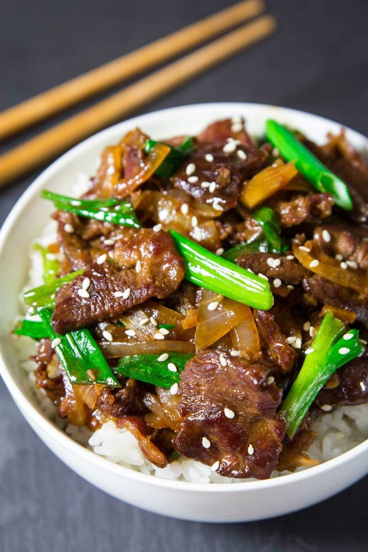 cooked Mongolian beef and green onion in a white bowl with white rice and chopsticks beside it. #beefandrice