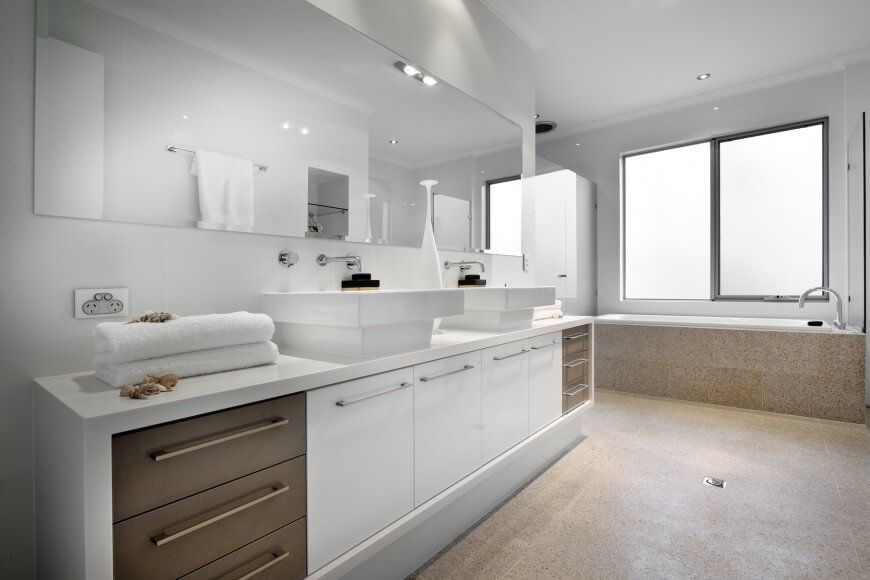 Bold White Bathroom Features Sleek White Cabinetry Paired With Natural Wood  Drawers In A Glossy Dual Vanity With Vessel Sinks. Speckled Tile Flooring  Rises ...