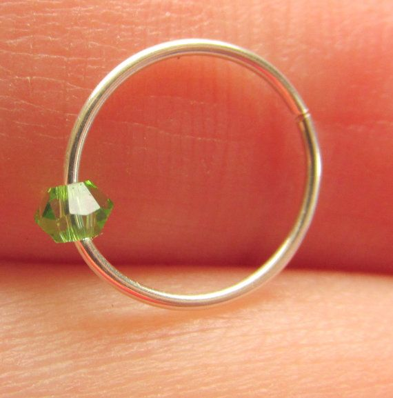This is for a SINGLE #hoop #ring perfect for your upper #ear, #nose, #eyebrow, or wherever else you have #pierced! This is not a cuff, it is an actual #piercing ring! The bead on it is a #Peridot #Swarovski Elements Bicone. It is loose, not glued, on the ring.  $6.25