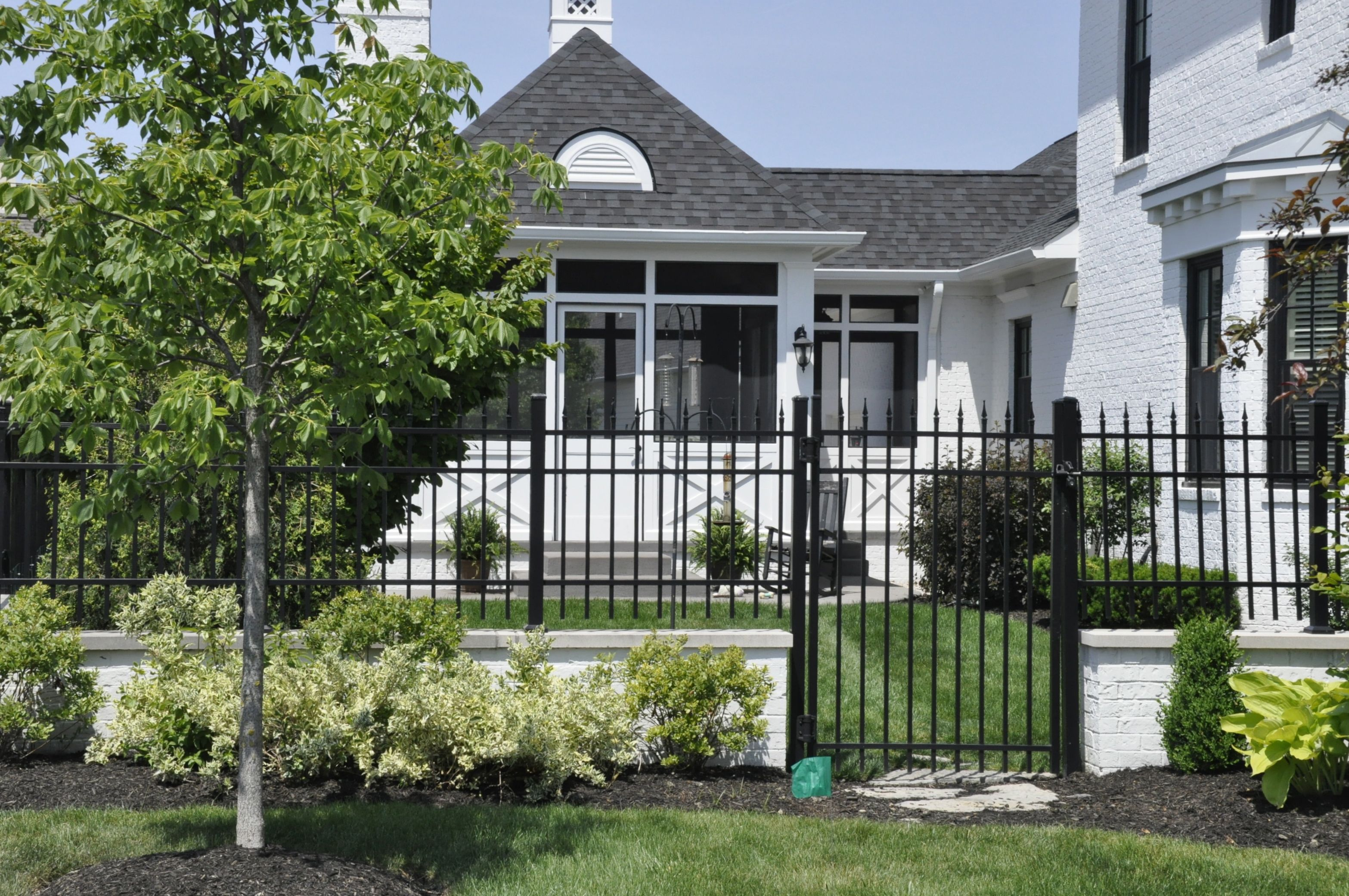 Crisp Black Wrought Iron Fence With White Brick Base