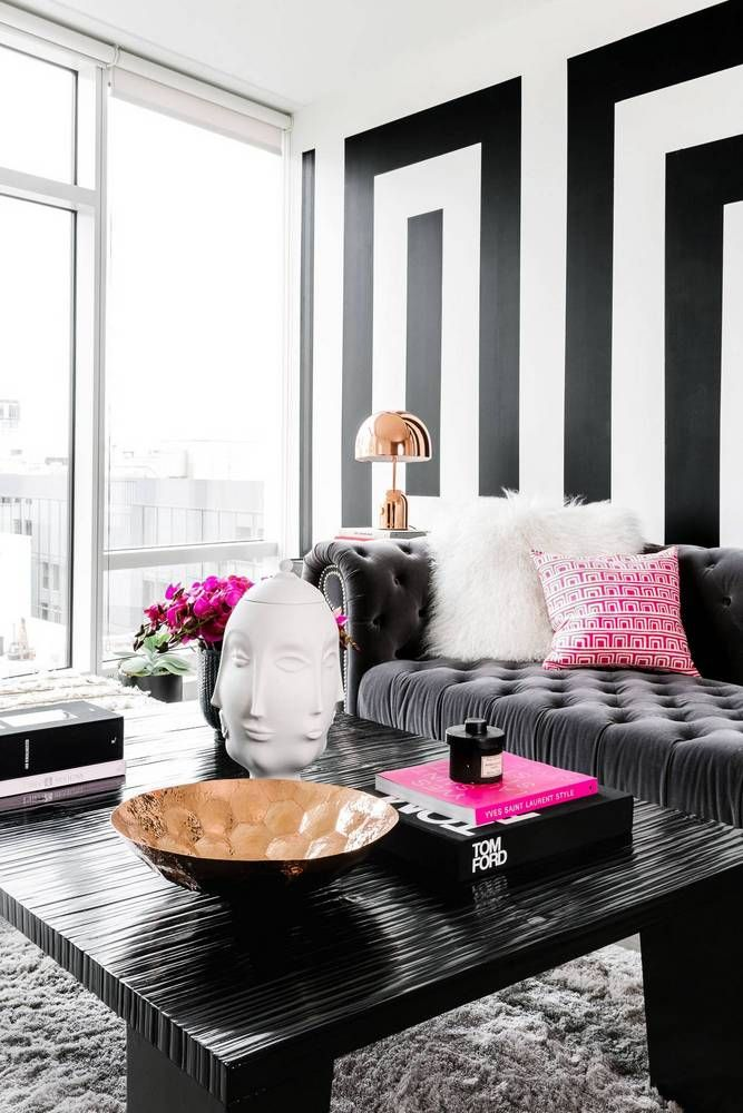 Monochrome living space with a gray sofa and a pop of pink
