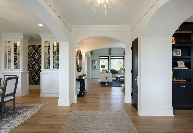The Front Door Opens To Wide Foyer With Arches And Hardwood Floors