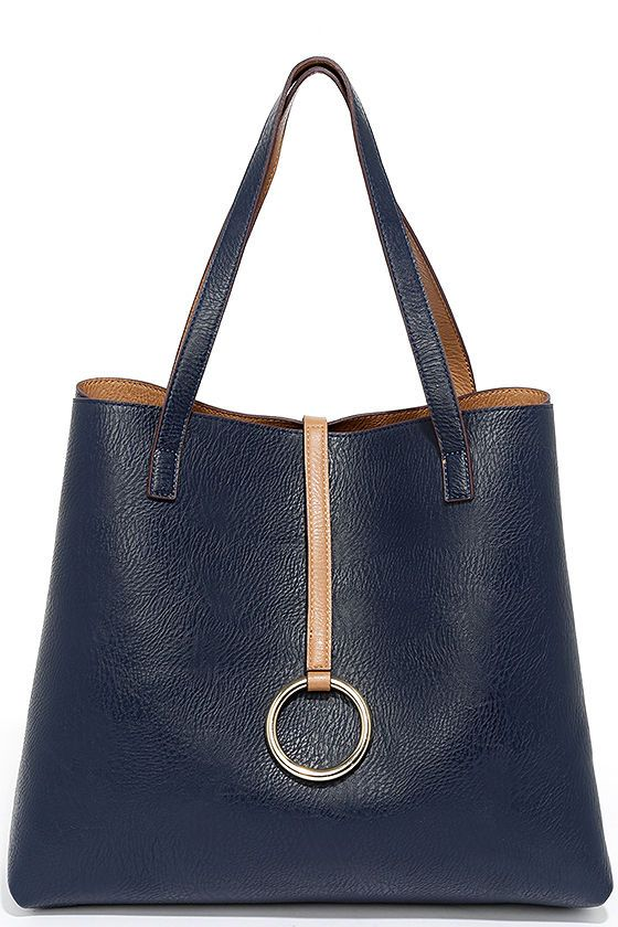 "With two stylish color options in one bag, the Flip the Script Navy Blue and Tan Reversible Tote is an easy choice! Tan vegan leather tote (with hidden magnet closure) has a decorative key ring strap, and roomy navy blue interior that reverses in a snap. Twin tote handles have a 9"" drop."