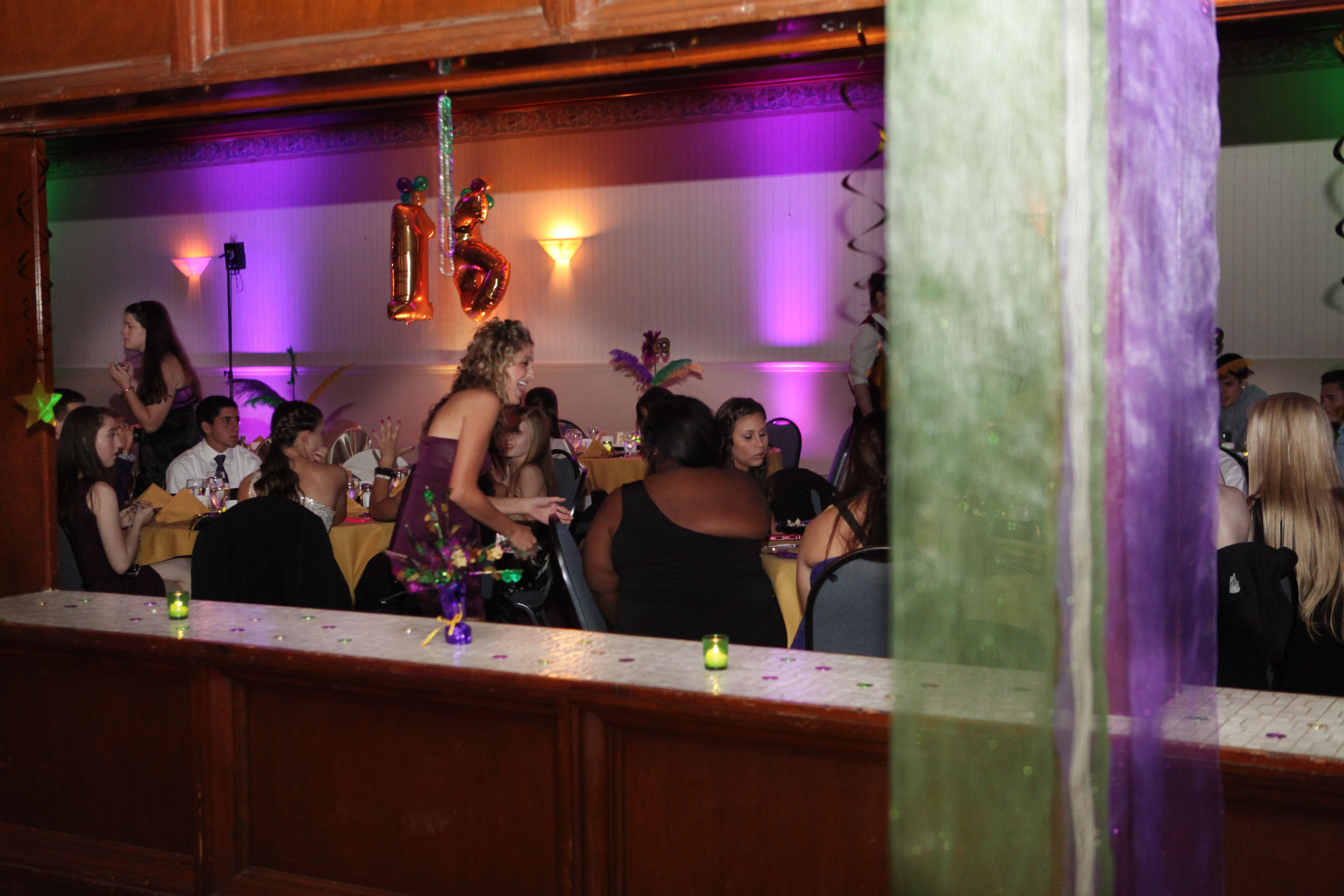 Gold, green, and purple shimmery ceiling-to-floor draping and Mardi Gras decor by Angelic Affairs, and uplighting in the theme's colors by GUE Productions