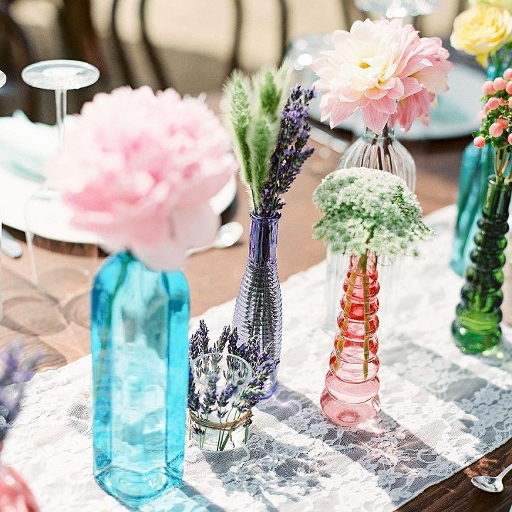 Various colored glass bottles filled in an array of flowers like peonies, hellebores, and thistles | wedding centerpieces