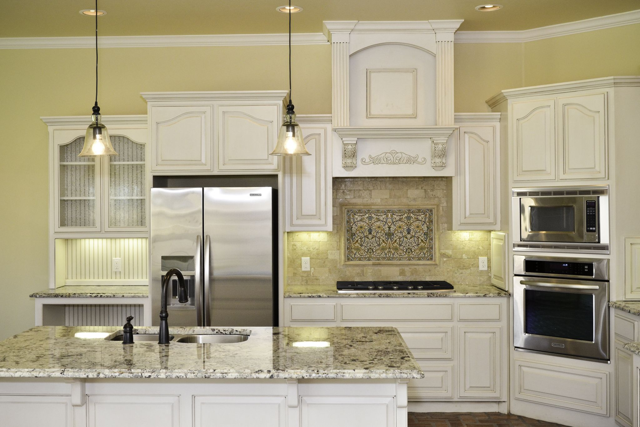 Traditional kitchen with glazed cabinets travertine backsplash hand painted tile and glass