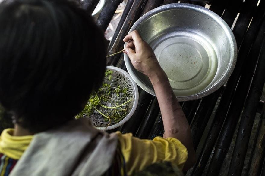 San Kay Khine, de 17 años, prepara algo de comer en Yangon, Birmania, donde muchos niños son maltratados y se ven obligados a trabajar. (Foto Prensa Libre: AFP).