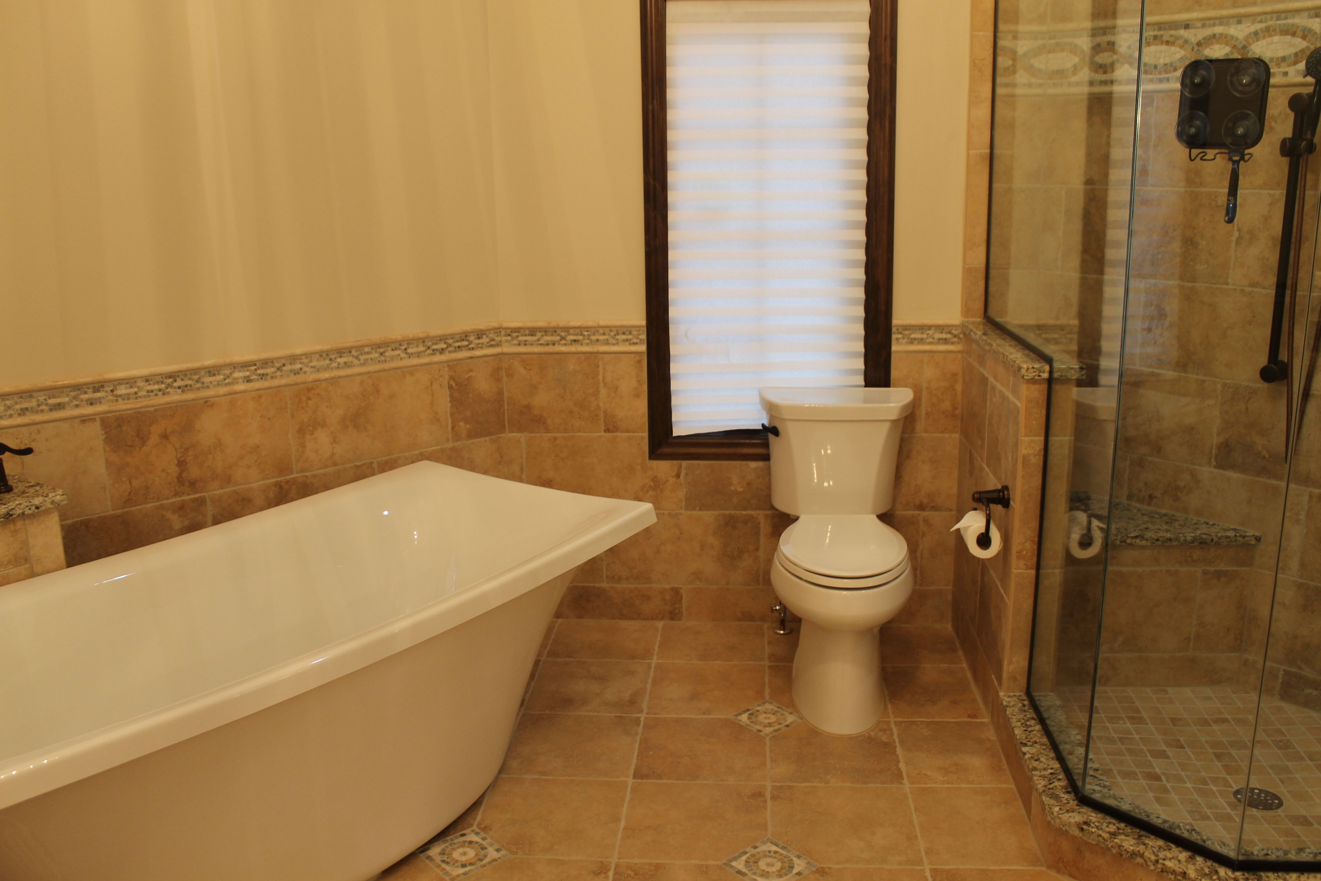 White Comfort Height Toilet between a Custom Tiled Shower and a ...