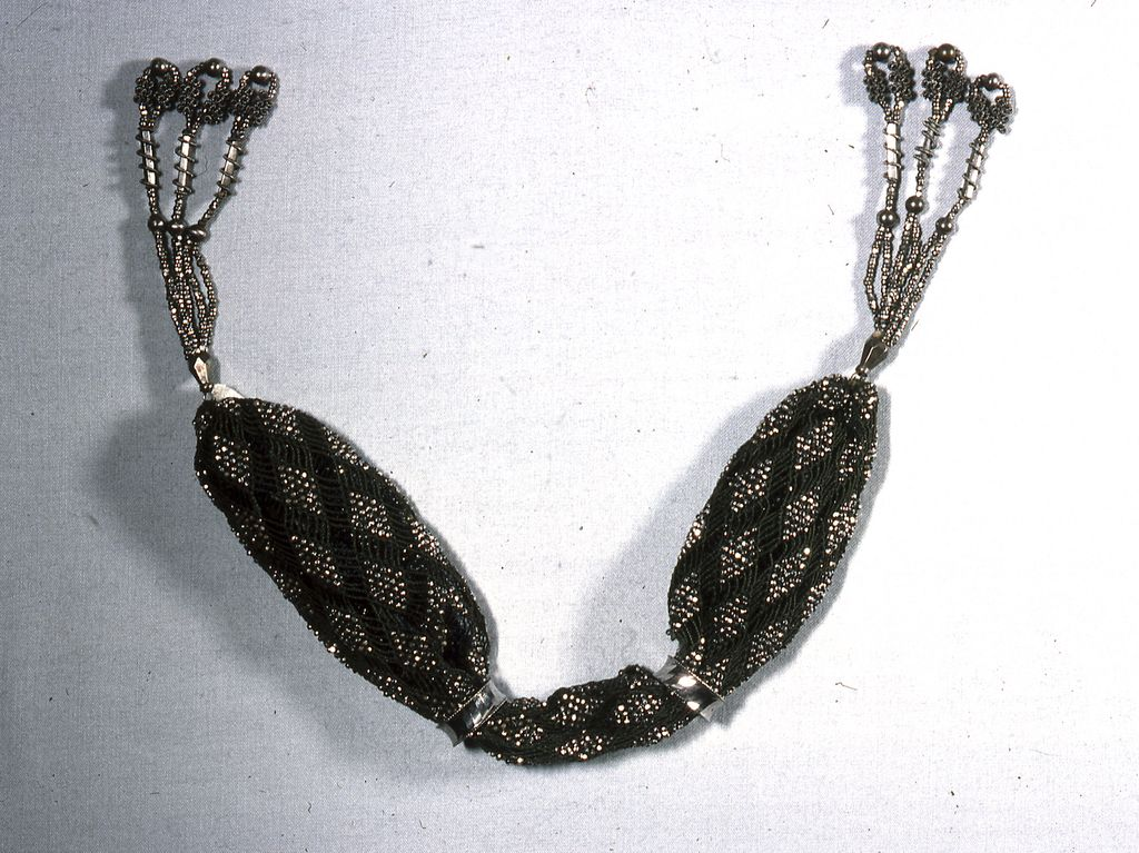 """Dark green silk net in which six threads cross each other at intervals forming diamond shapes, which are wholly covered by cut steel beads. Two steel rings control purse opening. Elaborate tassels at each end of cut steel bars, beads and twisted wire.    This miser's purse is medium: silk, metal technique: netting. Its dimensions are: L: 37.5 cm (14 3/4 in.).    This miser's purse is from France and dated """"1820–40""""."""