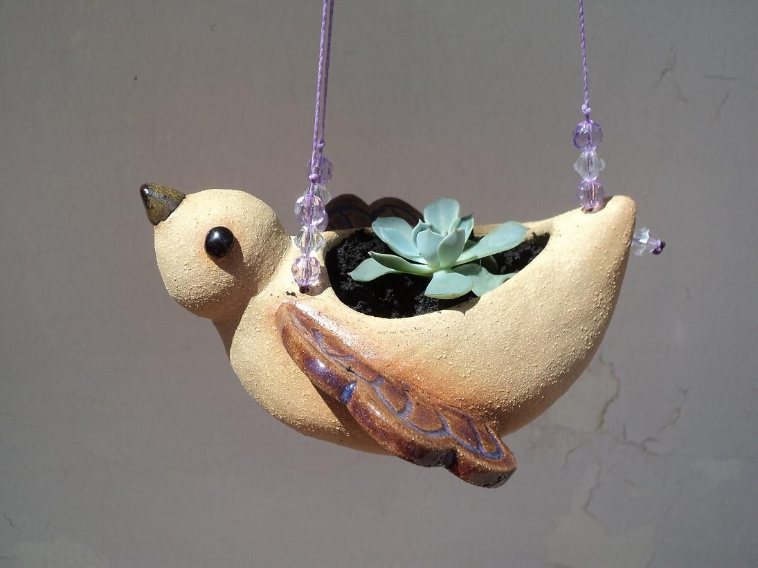 Vaso de pendurar feito em cerâmica de alta temperatura. <br>O fio é decorado com miçangas e o vaso tem furo para escoar a água. <br>Disponível nas cores dourado, azul claro, verde e violeta