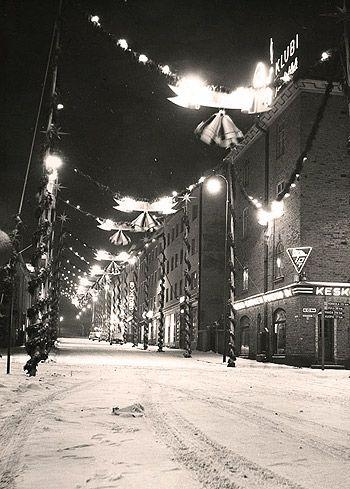 Joulunalustunnelmia Jyväskylän ensimmäiseltä joulukadulta,  Väinönkadulta.1950-luvun katukuvia koristavat havuköynnöksin  kiedotut salot, valaistut tähdet ja lyhdyt sekä joulukellot. Valokuva: Seppo Turpeinen.