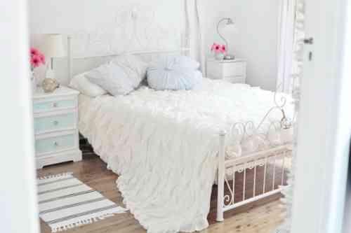 chambre à coucher blanche de style Shabby chic avec une literie fine