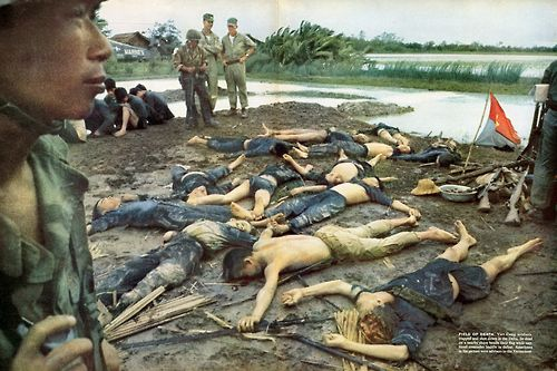 Vietcong soldiers, trapped and shot down in the Delta, lie dead on a nearby shore while captured comrades sit near American advisers.