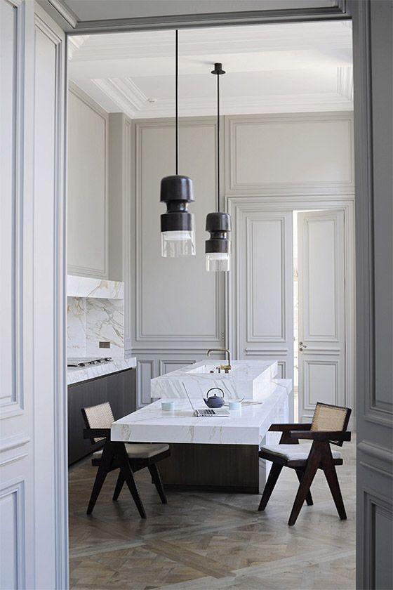 Joseph Dirand Paris luxe minimal kitchen white marble gray molding Pierre Jeanneret chairs bronze pendants