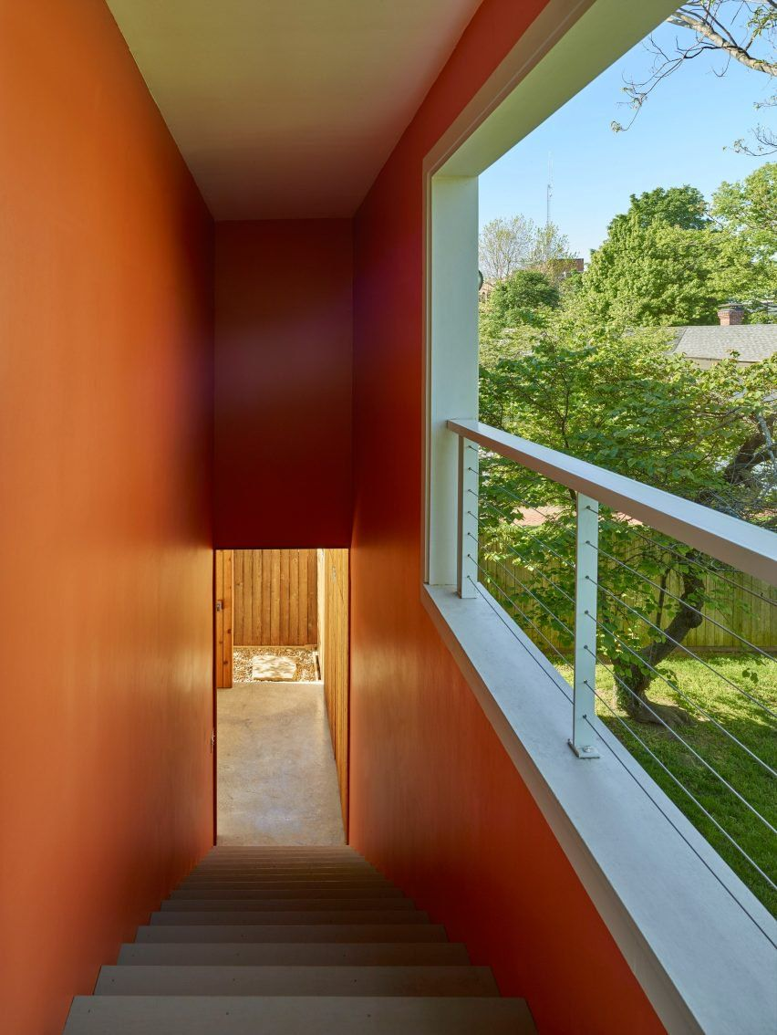 A glazed front door is located on the rear elevation of this American house extension, which overlooks the backyard. The team used the colour orange to articulate the stairway and entrance.