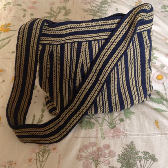 Striped Shoulder Bag from Ten Thousand Villages In navy blue and yellow, and blue interior with 5 x 5.5 inch striped pocket. Top opening is about 11 inches long so not big enough for a school binder, but great for carrying beach reading. Magnetic snap closure. Handmade in India by hand-weaving cotton strips together with the use of floor looms, then sewing them together. Ten Thousand Villages Bags Shoulder Bags