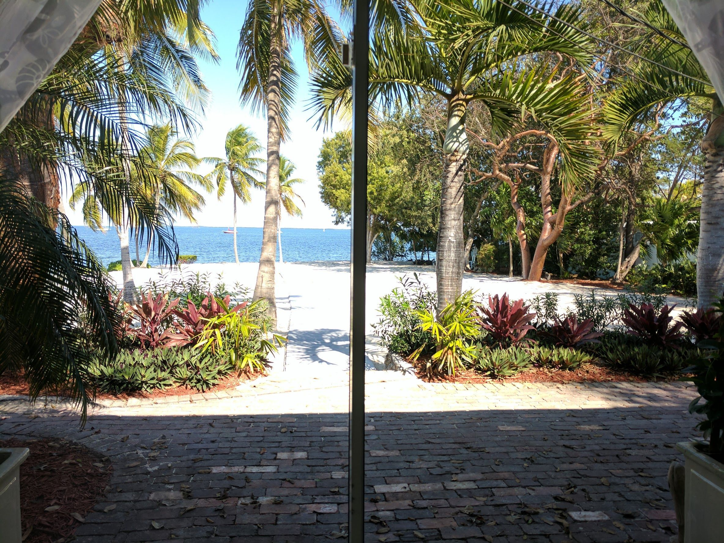 Wedding beach house  View to Ceremony site from Brideus suite very tropical ambience