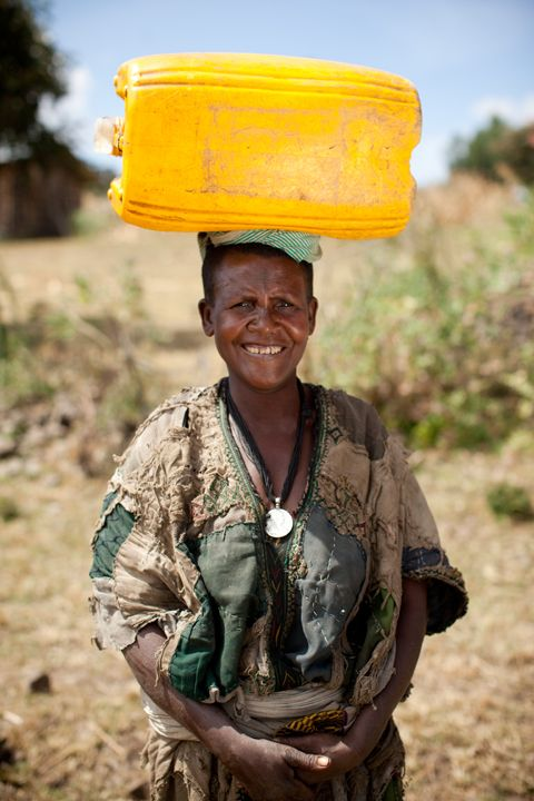 A woman carries water home to her family from a charity: water well in Agam Minch, Ethiopia.
