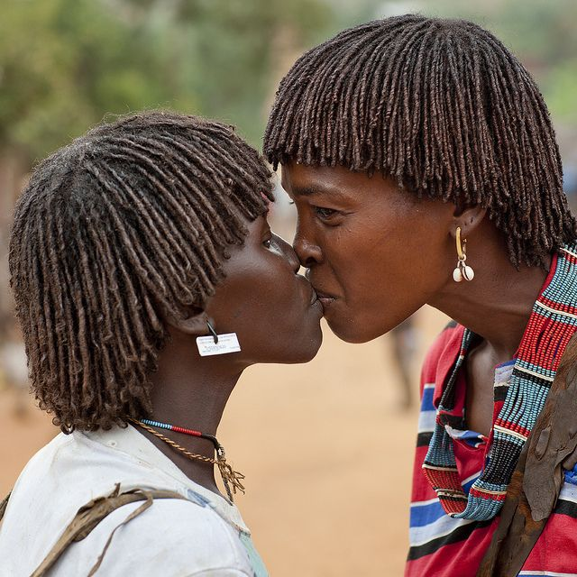 Bana women saying hello - Ethiopia    Many tribes use a kiss on the lips to say hello to each others. The Bana do it, but to foreigners, they shake hands!