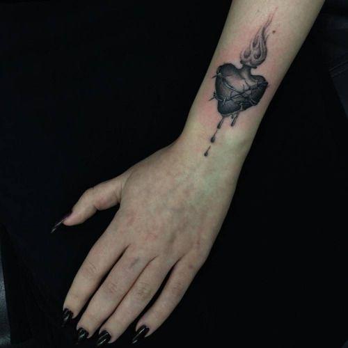 Pequeño Tatuaje De Un Corazón En Llamas Situado En La Muñeca