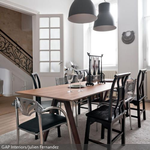 Wände, Tür- und Fensterrahmen sowie Teppich sind in Weiß gehalten. Um diesem hellen Esszimmer mehr Kontur zu verleihen, ist der Esstisch umzingelt von Holzstühlen…