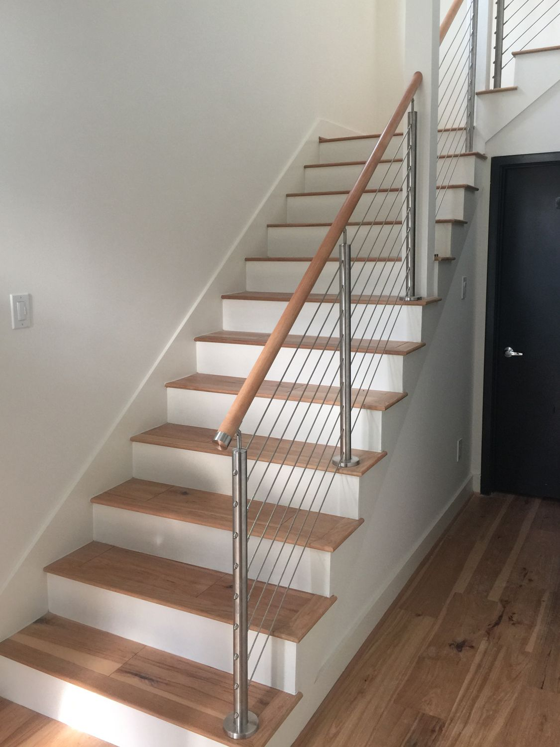 Our Stainlesssteel Wire Rope Railing With Wood Rail Makes A Modern Statement All Can Appreci Stairs Design Modern Stairs Design Interior Staircase Design