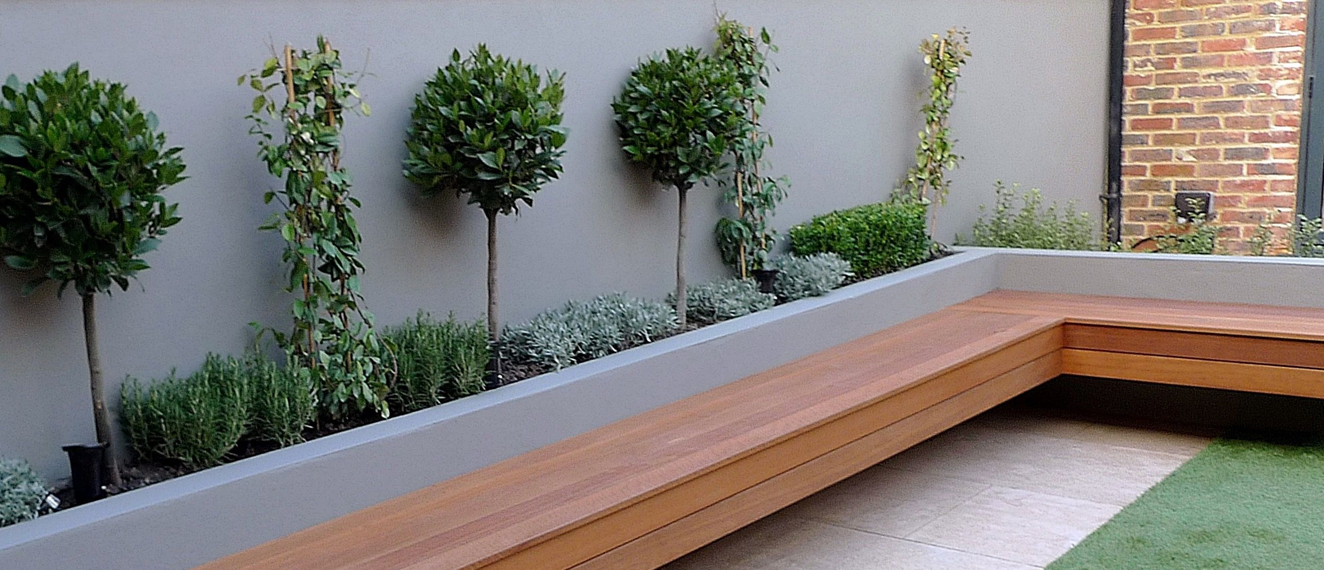 raised beds artificial grass hardwood strip travertine paving