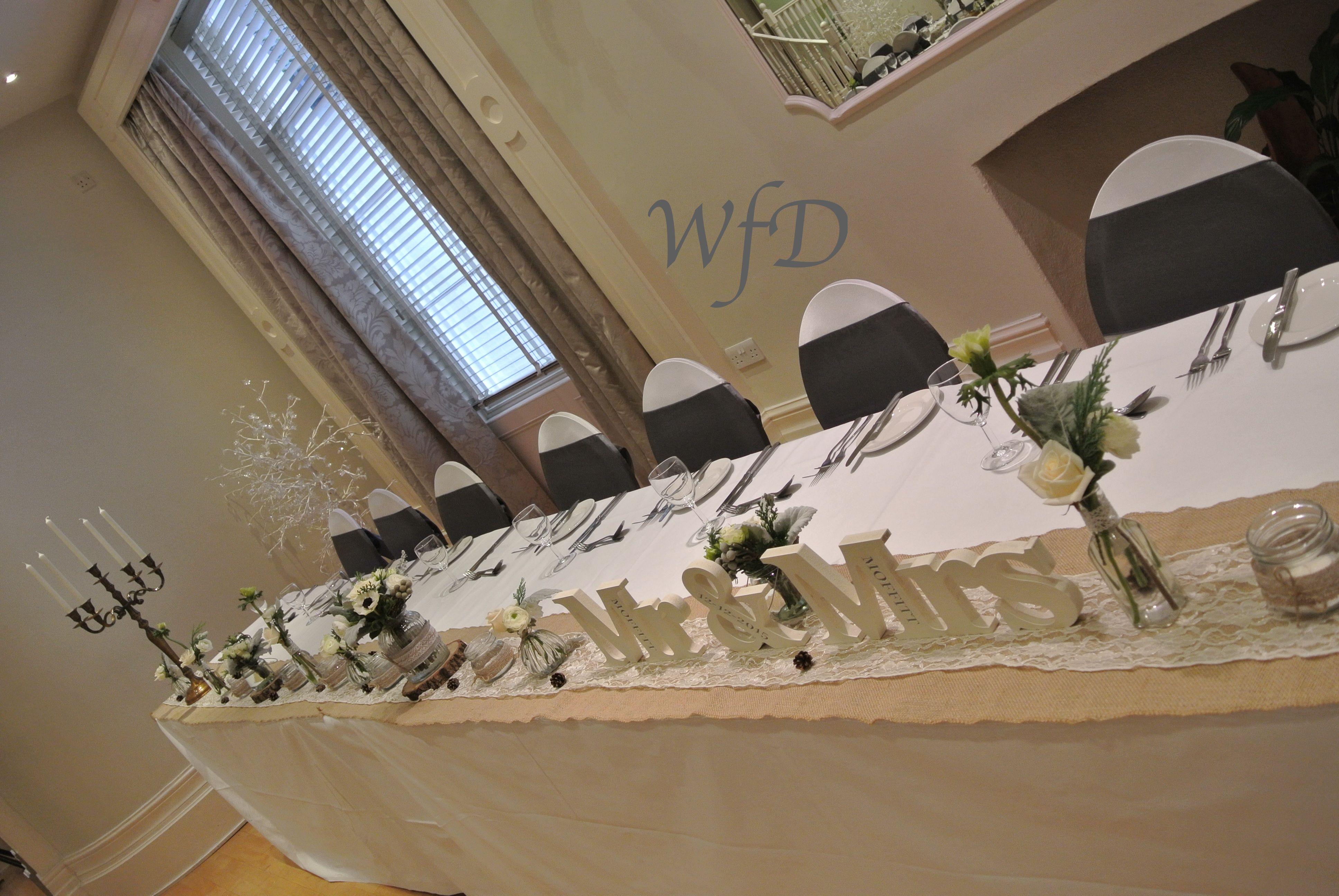 Bottles, jam jars, flowers, hessian, lace top table wedding at the Royal seven stars Totnes Devon