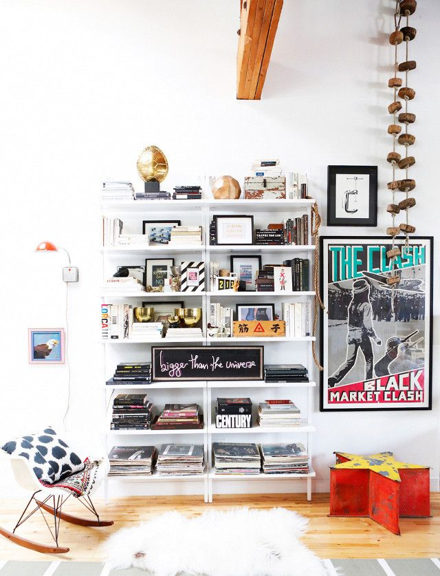 Eclectic loft living space with a wall of books, large art, and a Eames rocking chair