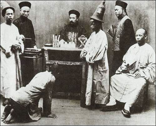 """The photo shows a magistrate and his half a dozen assistants interrogating a single """"subject"""" at his office."""