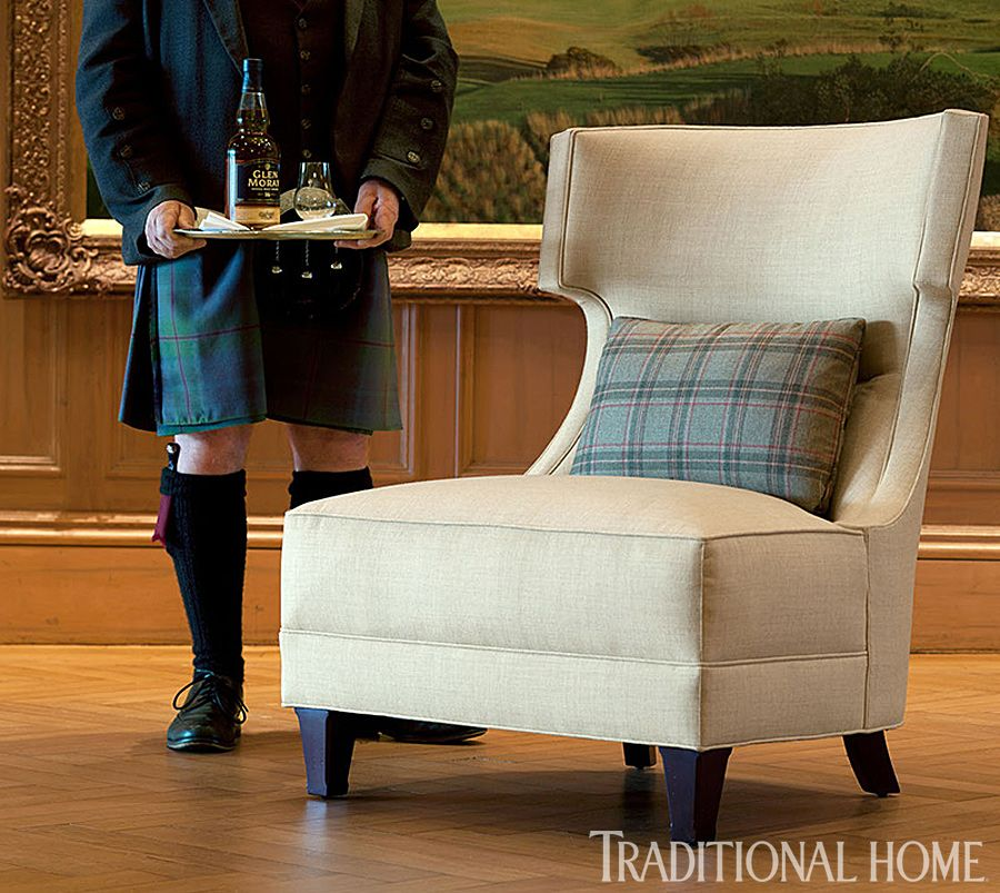 """The """"Sorbonne"""" wing chair from Jacques Garcia's collection for Baker wears a subtle strié in """"Islay Twill Citrus"""" and is topped with a pillow in """"Taransay Olive"""" plaid, both from The Isle Mill. - Traditional Home ® / Photo: Dominic Blackmore"""