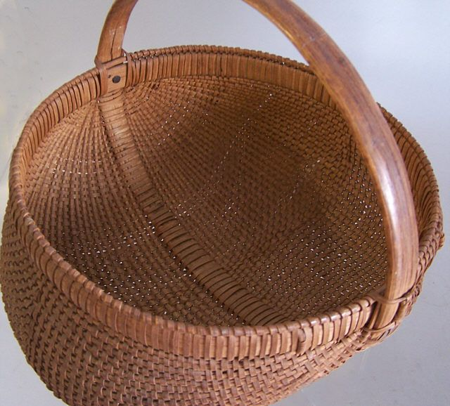 ITEM# 5817      Antique Appalachian oak splint buttocks gathering basket by Mary Clausby Burke county North Western Mountains of North Carolina. c1900. This is the best buttocks basket we have ever seen. Tight weaving, perfect patina, excellent condition. The unusual twist knot on the handle was her signature. This basket is a 10. Measures 12 inches by 11 inches by 9 and one half.    Antique Appalachian oak splint buttocks gathering basket