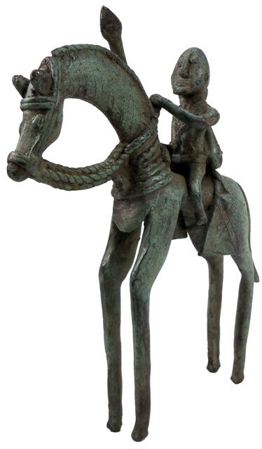 """Sadigh Gallery's African Dogon Tribe Bronze Statue of Horseman.  African, Dogon Tribe. Bronze horseman, the rider with a spear in the right hand, the left arm holding the reins, bow and arrows to the back, the horse with a braided saddle and bag, incised lines to the neck, both elongated in design. Traces of green patina. 1800's AD (7 ¾"""" x 6"""")"""