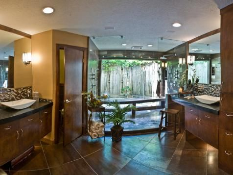 This tiled master bathroom has an Indonesian feel, from the wood finishes to the walk-in spa shower with a bench and an outdoor view.