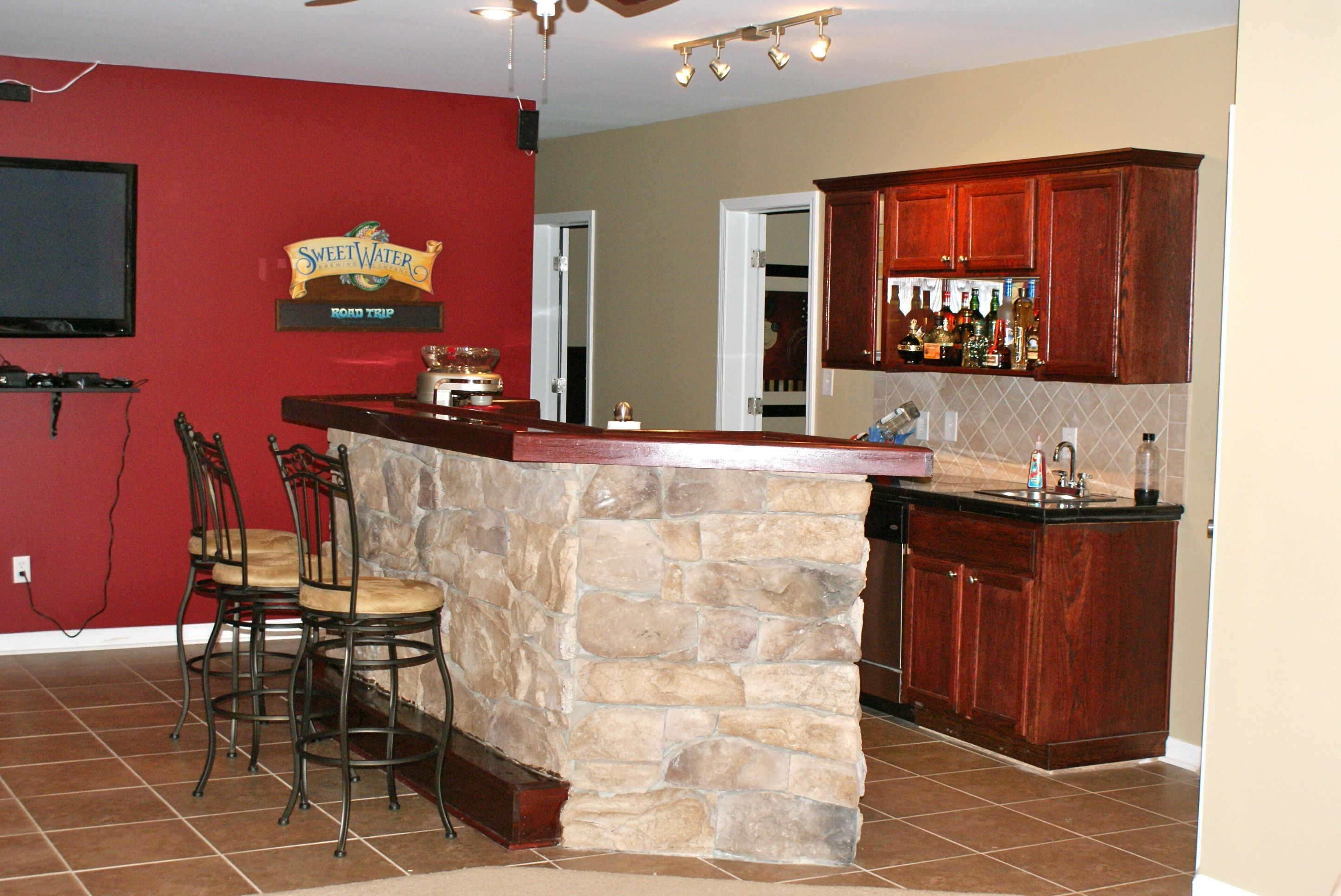 Red wall and stone bar counter also wood bar cabinet and for Home bar designs and ideas