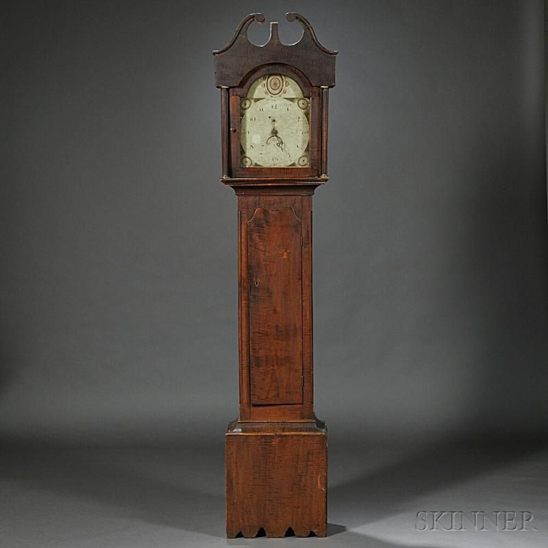 New England Tiger Maple Tall Clock, c. 1810, scroll-top case above the freestanding reeded columns, painted Arabic numeral dial with geometric and floral spandrels and arch decoration, serpentine waist door, cove molded base with scalloped apron, thirty-hour time and hour strike, pull-up movement, ht. 89 in.