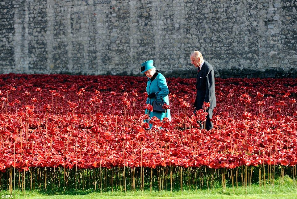 With almost all of the 888,246 poppies now in place, the Queen was rendered almost invisible as she walked through the sea of ceramic crimson blooms during a tour of the Blood Swept Lands and Seas of Red installation at the Tower of London this morning - 16th October 2014