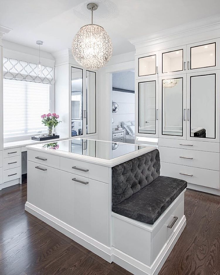 Luxurious Walk In Closet Boasts An Ornate Chandelier Hung Over A Mirror Top White Center Island Finished With Satin Nickel Pulls And Built Bench Topped